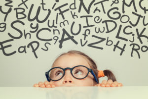 little girl with handwritten letters of alphabet above her head